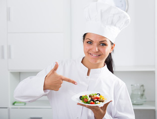 Woman cook holding plate of salad