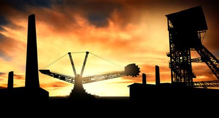 Coal mine with big excavator machine at sunset