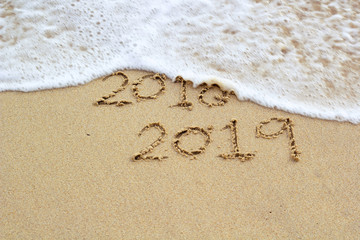 New Year 2019 sign in tropical beach sand with turquoise ocean