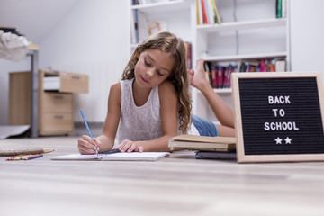 Cute schoolgirl smiling and sitting on the floor. drawing on a notebook at home. Letter board with Back to school concept. Pencils and notebook besides.