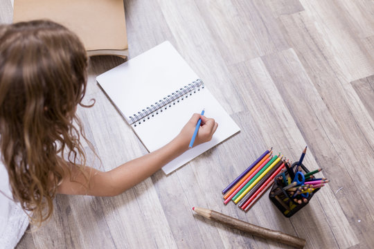Cute schoolgirl sitting on the floor and drawing on a notebook. brown wood background. Back to school concept. Pencils and notebook besides. top view