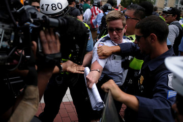 Police push back journalists to clear a path for white nationalist demonstrators at the Foggy Bottom rail station in Washington