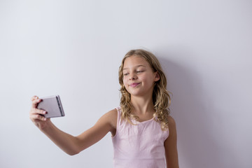 portrait of a young beautiful kid using a mobile phone and taking a selfie. white background. Kids indoors. Lifestyle