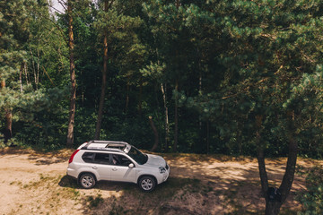 white suv in forest. aerial view. car travel concept