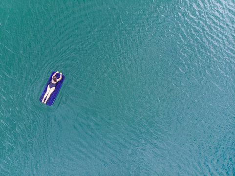 woman on mattress in azure water. overhead view. copy space