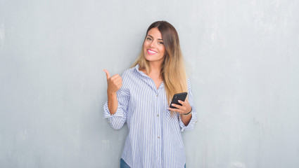 Young adult woman over grey grunge wall looking at smartphone texting a message happy with big smile doing ok sign, thumb up with fingers, excellent sign
