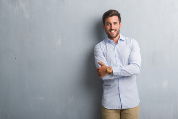 Handsome young business man over grey grunge wall wearing elegant shirt happy face smiling with crossed arms looking at the camera. Positive person. Fototapete