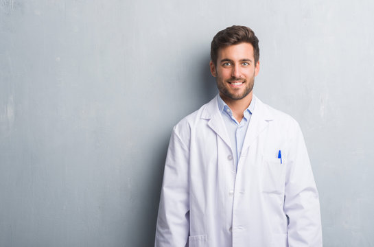 Handsome young professional man over grey grunge wall wearing white coat with a happy and cool smile on face. Lucky person.