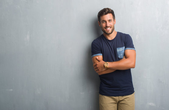 Handsome young man over grey grunge wall happy face smiling with crossed arms looking at the camera. Positive person.