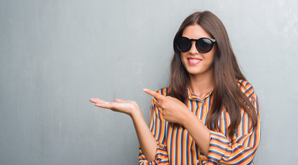 Young brunette woman over grunge grey wall wearing big sunglasses very happy pointing with hand and finger