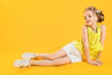A teenage girl is sitting on a yellow background.