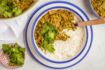 Lentil curry with rice, Indian cuisine, tarka dal, white background, top view. Vegan food.
