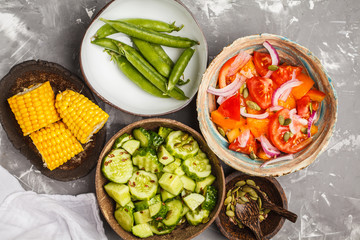Clean eating concept. Cucumber salad, tomato salad, flax bread, avocado, corn. Top view, food background.