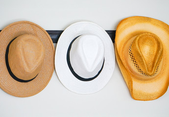 A variety of hats hung on a hook