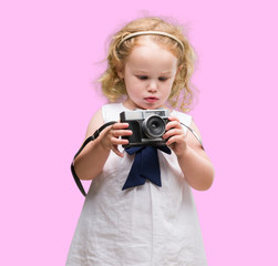 Beautiful blonde toddler taking pictures with vintage camera