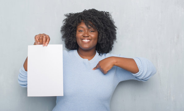 Young african american woman over grey grunge wall holding blank paper sheet with surprise face pointing finger to himself