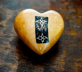 A Black and White Emblem painted on a stone heart