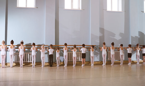 The training of young dancers in the ballet studio. Young dancers perform gymnastic exercises at the ballet or barre while warm-up in the classroom.