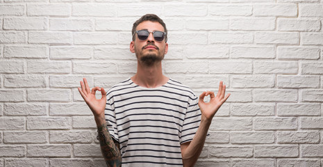 Young adult man wearing sunglasses standing over white brick wall relax and smiling with eyes closed doing meditation gesture with fingers. Yoga concept.