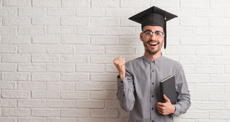 Young adult man over brick wall wearing graduation cap screaming proud and celebrating victory and success very excited, cheering emotion