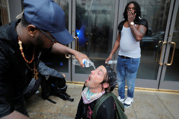 A counter-demonstrator has his eyes doused with water during a white nationalist-led rally marking the one year anniversary of  the 2017 Charlottesville 'Unite the Right' protests in Washington