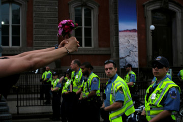 M.O. Williams of Alexandria, Virginia holds a bouquet of flowers out in front of police officers guarding the White House on Pennsylvania Avenue in Washington