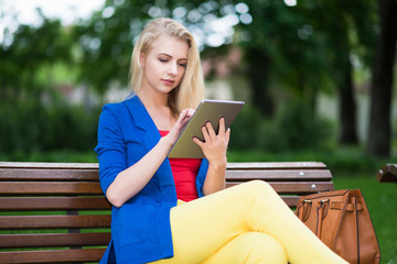 Woman using her tablet in a park