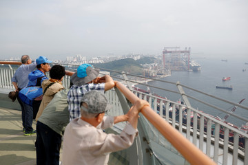 People watch Hyundai Heavy Industries from an observatory platform in Ulsan
