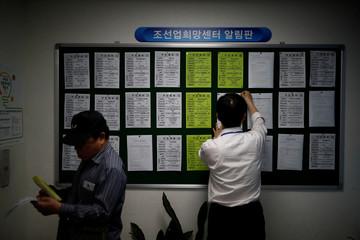 An employee hangs a job advertisement at a job center in Ulsan