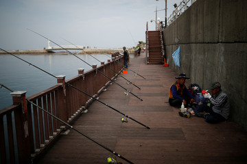 People fish at a port in Ulsan