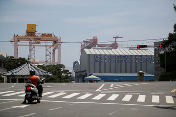 A man on a motorbike waits for a traffic signal in front of Hyundai Heavy Industries' Shipyard in Ulsan