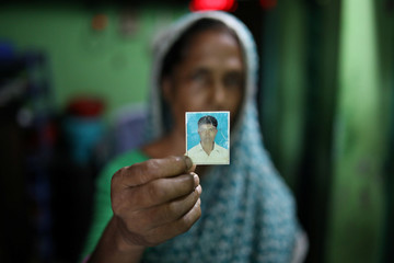 Rina Begum holds a photograph of her son Riazul Islam, alleged drug dealer who was killed by police in Tongi, Gazipur
