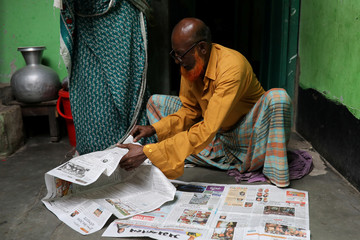 Hafiz Mia flips through the newspapers, for news of his son Riazul Islam, an alleged drug dealer who was killed by police in Tongi, Gazipur