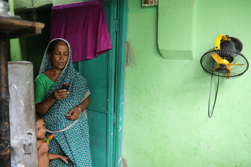Rina Begum, the mother of Riazul Islam, alleged drug dealer who was killed by police, uses a mobile phone in Tongi, Gazipur