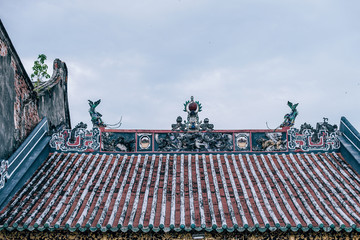 Traditional Chinese temple red weathered rooftop with white lines. At the top of the roof, there are mini statues and ornaments are against the clear blue sky. The photograph on a bright daylight.