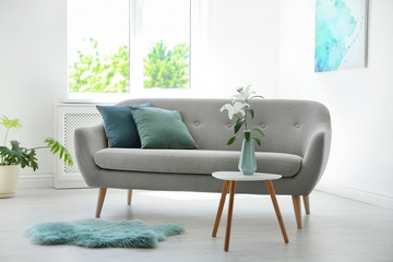 Stylish living room interior with sofa and mint decor elements