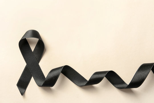 Black ribbon on light background, top view. Cancer awareness