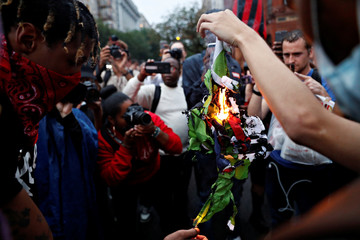 """Opponents of a white nationalist-led rally marking the one-year anniversary of the 2017 Charlottesville """"Unite the Right"""" protests, set a Kekistan flag on fire in downtown Washington"""