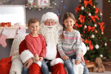 Little children sitting on authentic Santa Claus' knees indoors