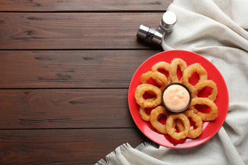 Plate with fried onion rings and sauce on table, top view