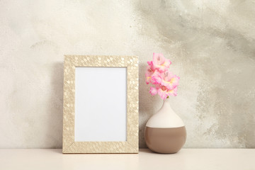 Blank frame and vase with flowers on table near color wall. Mock up for design