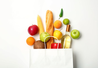 Flat lay composition with shopping bag and products on white background