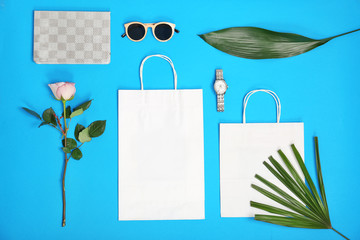 Stylish flat lay composition with shopping bags on color background