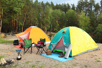 Camping tents and accessories in wilderness on summer day