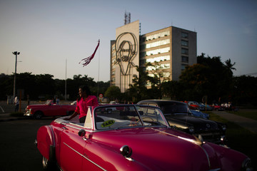 A tourist has a picture taken by a taxi driver in a vintage car at Plaza de la Revolucion in Havana, Cuba