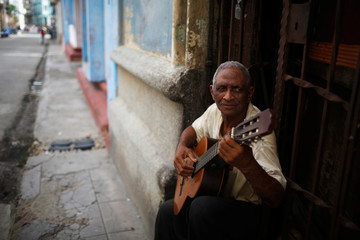 A man plays guitar outside his house in Havana
