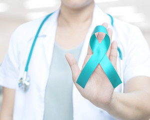 Teal ribbon awareness on doctor's hand for Ovarian Cancer, Polycystic Ovary Syndrome (PCOS) disease, Post Traumatic Stress Disorder (PTSD), Tourette's Syndrome, Obsessive Compulsive Disorder (OCD)