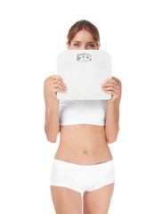 Happy slim woman satisfied with her diet results holding bathroom scales on white background