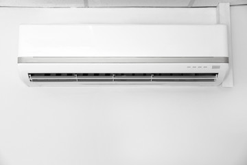 Modern air conditioner on white wall indoors