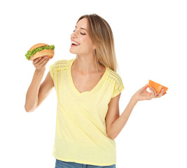Young woman holding burger and grapefruit on white background. Choice between diet and unhealthy food